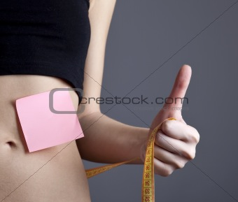 Beautiful and strong women's abs with metre and note.