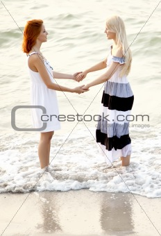 Two beautiful young girlfriends jumping on the beach