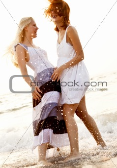 Two beautiful young girlfriends on the beach