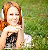 Young fashion girl with headphone lying at green grass