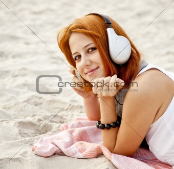 Portrait of red-haired girl with headphone at beach.