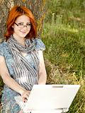 Young smiling fashion girl in glasses and notebook sitting near