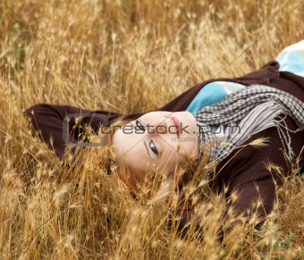 Young beautiful girl lying at yellow autumn field.