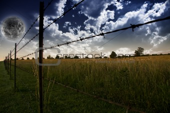 Sky with clouds and Farmers Fence and field