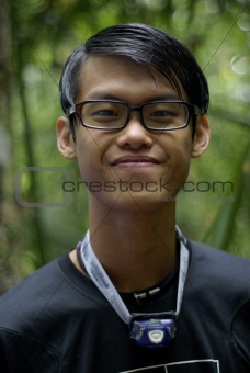 Slick hair asian man with spectacles smiling outdoors