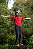 Asian man with outstretched arms at peace with nature outdoors