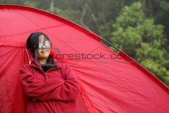 Asian malay teen girl standing beside red tent outdoors
