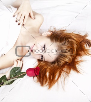 Beautiful red-haired girl with rose in the bedroom.