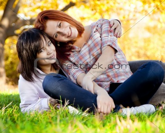 Two beautiful teen girls in green grass in the park.
