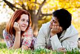 Young couple in grass in the park.
