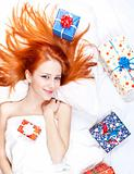 Happy red-haired girl in bed with Christmas gifts.