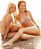 Two beautiful young girlfriends in bikinis on the beach