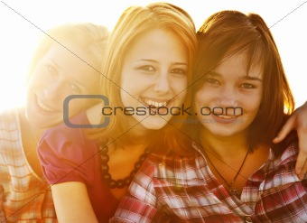 Portrait of three beautiful girls. With counter light on backgro