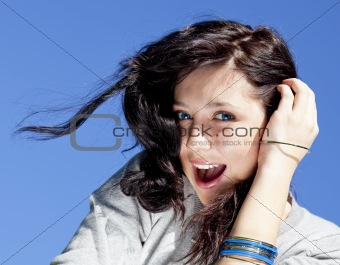 Portrait of beautiful brunette girl on blue sky background.