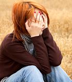 Lonely sad red-haired girl in field