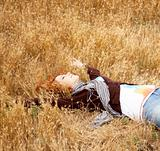 Young beautiful girl lying in yellow autumn field.