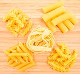 Different kinds of italian pasta on the wooden background