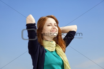 Portrait of red-haired girl on blue sky background.