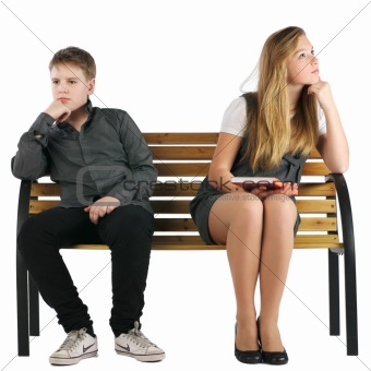 Boy and girl sitting on a bench and not looking at each other