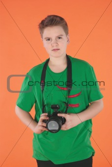 Boy with photo camera. Orange background