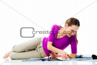 woman lying on the floor reading a magazine on white background studio