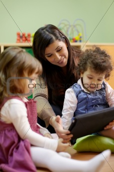 Teacher reading fairy tale to children at school