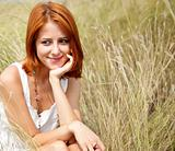 Beautiful red-haired girl at grass