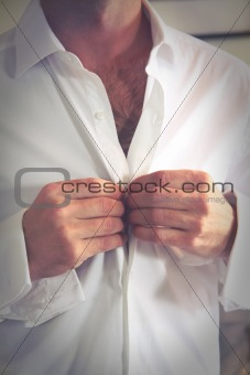Groom buttons his shirt before the wedding