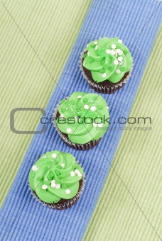 Top of Chocolate Cupcakes with Green Frosting on Blue Mat