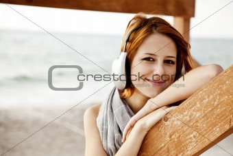 Portrait of young red-haired girl in headphone near wood at beach