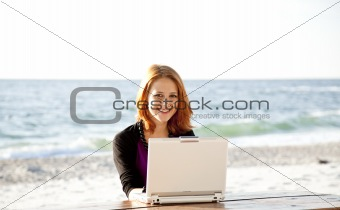 Portrait of red-haired girl with laptop at beach.