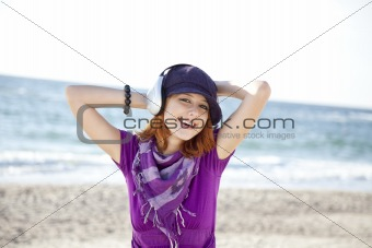 Portrait of red-haired girl with headphone on the beach.