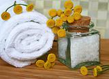 White bath towel, bottle of sea salt in spa composition