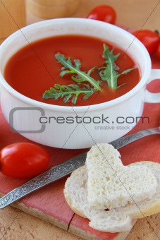 tomato soup in a white bowl with arugula and cherry tomatoes