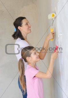 Mother and daughter painting a wall with roller