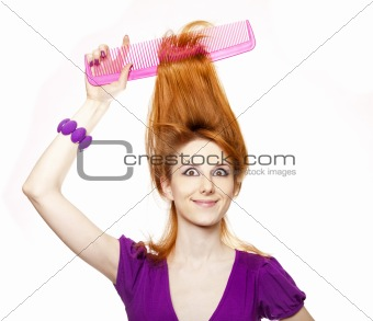 Funny red-haired girl with big comb.