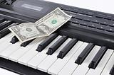 Dollar lying on the keys of old synthesizer