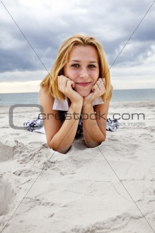 Beautiful blond girl lying on sand at the beach in rainy day.