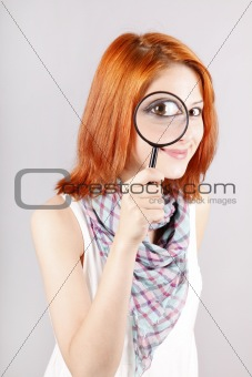 Beautiful red-haired girl with loup zooming her eye.