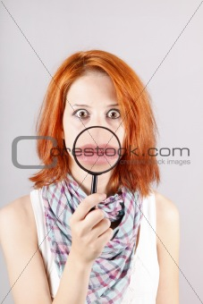 Beautiful red-haired girl with loupe zooming her mouth.