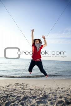 Beautiful brunet girl jumping on the beach.
