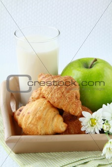 Fresh breakfast croissants, milk and a green apple