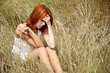Sad red-haired girl at grass.