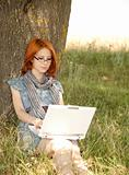 Young redheaded woman using laptop outdoors