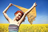 Young woman with open arms keep yellow silk on wind.