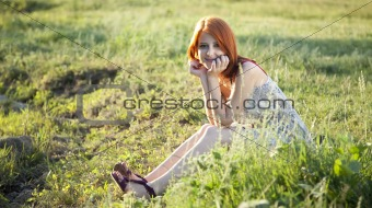 Girl at grass field at sunset. Photo in old image style.