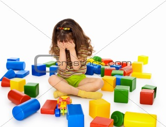 Little girl sitting on white among toys and crying