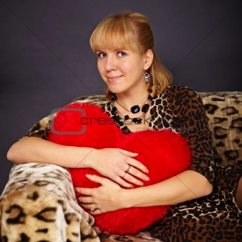 Beautiful young woman with toy heart in hands
