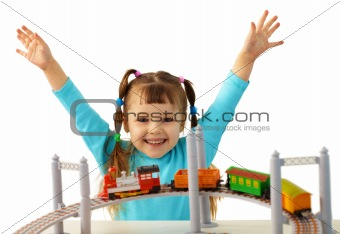 Joyful girl playing with toy railway