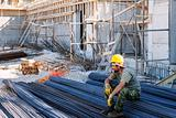 Construction worker resting on steel bars